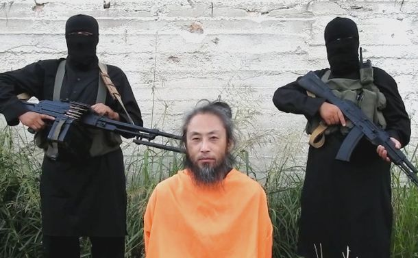 写真・図版 : 2018年7月にインターネット上で公開された安田純平さんとみられる男性(中央)が映った動画の一場面。いつ撮ったのか時期の分からない動画は、「今現在も生きている」と確定させる生存証明にはなりえない。「救けてください」というのも100%言わされているだけなので、これを真に受けて「救けなければ」と考える専門家はいない。