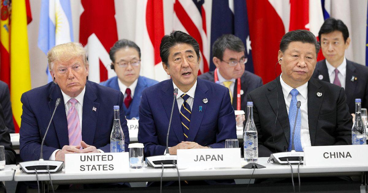写真・図版 : 「G20」サミットで行われた首脳特別イベントであいさつする安倍晋三首相(中央)。左はトランプ米大統領、右は中国の習近平国家主席=2019年6月28日