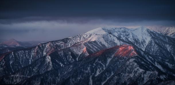 写真・図版 : 厳冬期北アルプス西穂高岳の稜線にて、朝日が一瞬顔を出し山の一部を淡く染めた