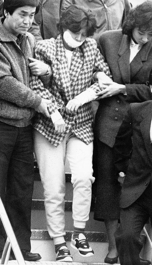 写真・図版 : 1987年12月、大韓航空機爆破を実行した疑いで韓国に移送される金賢姫容疑者。死刑判決が確定した後、特赦された=ソウル金浦空港、東亜日報提供