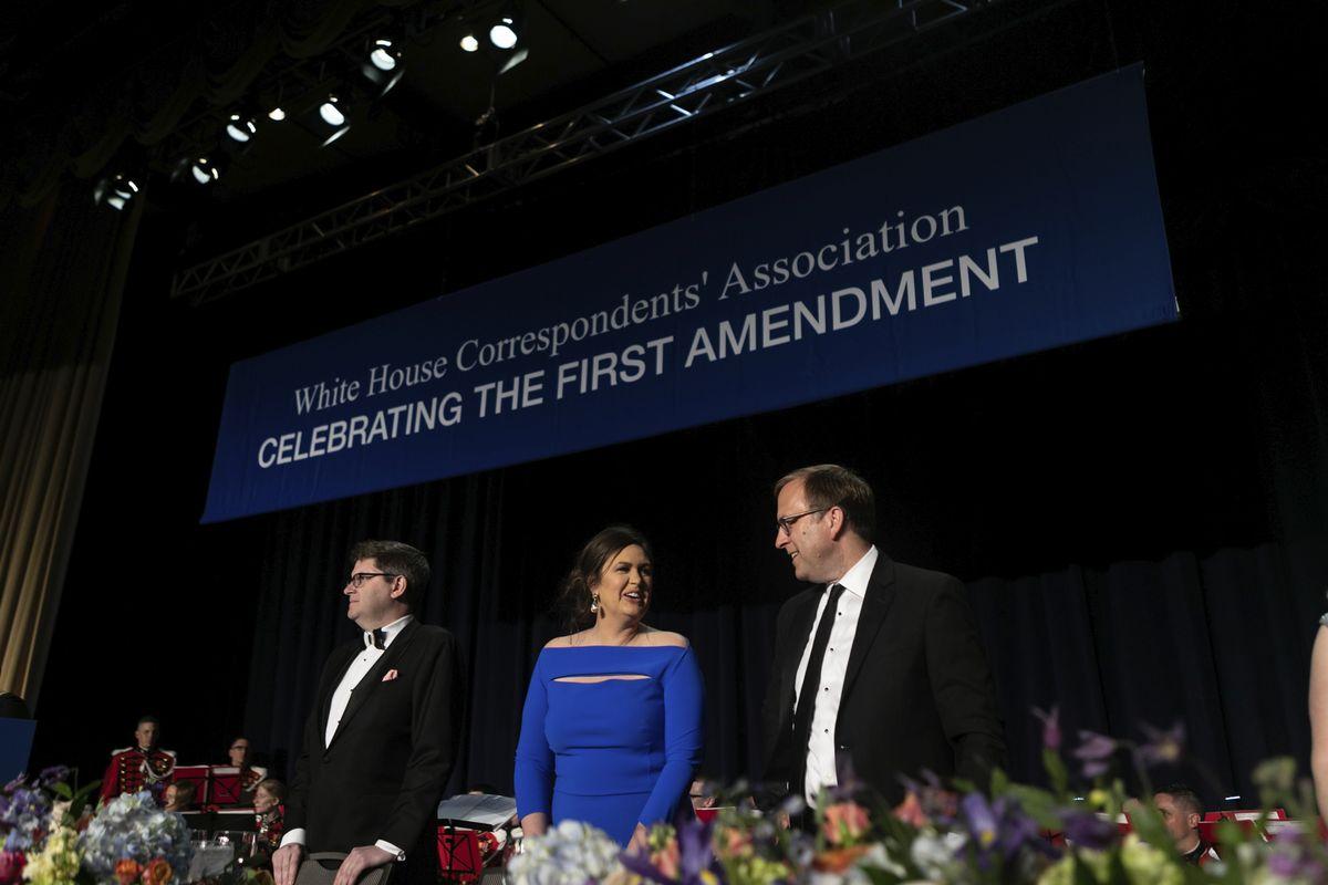 写真・図版 : ワシントンDCのワシントンヒルトンで開催されるホワイトハウス特派員協会の晩餐会に招かれたサンダース報道官(中央)=2018年4月28日、AP