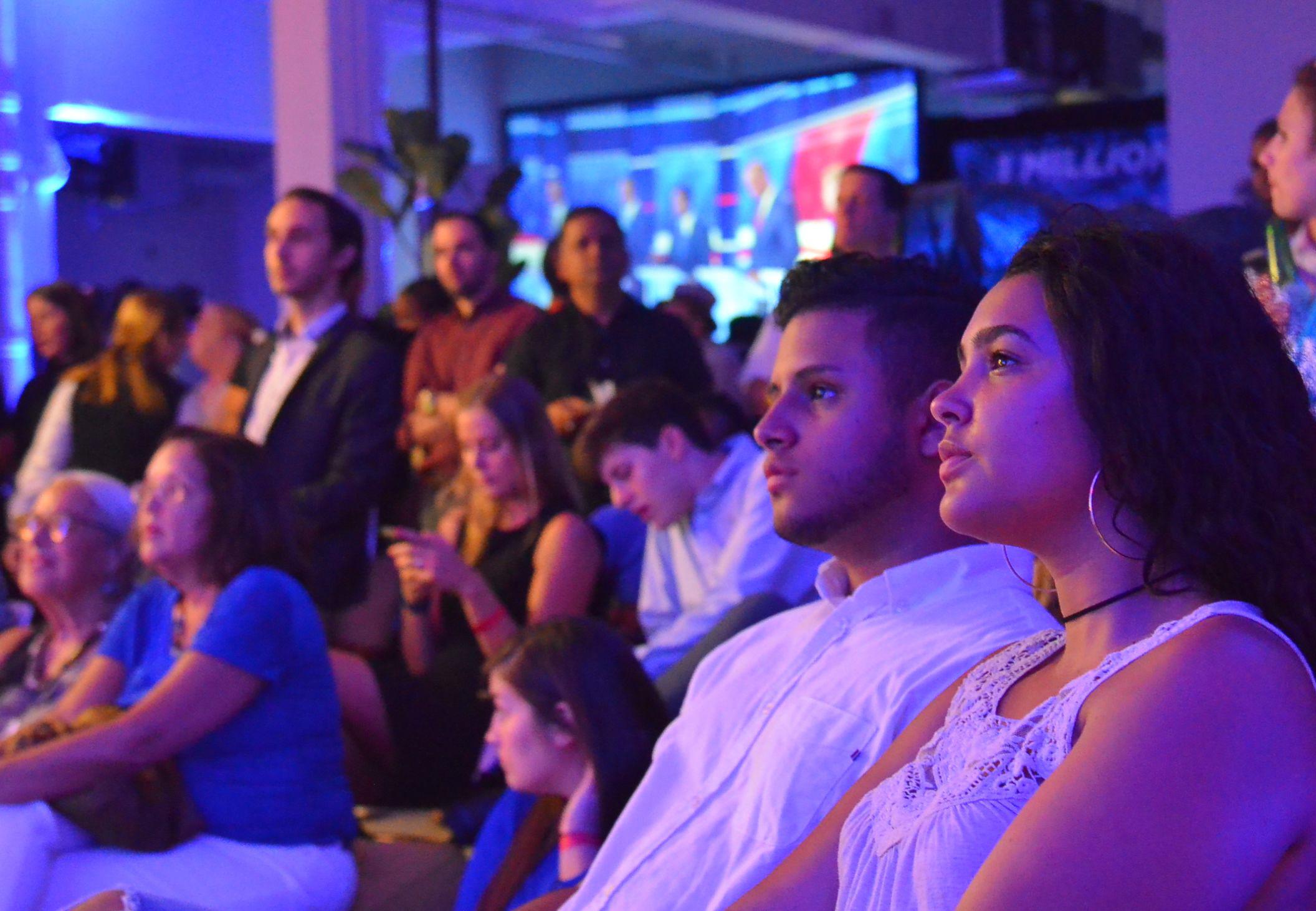 写真・図版 : 民主党の団体が主催したテレビ討論会の観戦パーティーで、発言する候補者を見つめる支持者ら=2019年6月27日、マイアミ、土佐茂生撮影