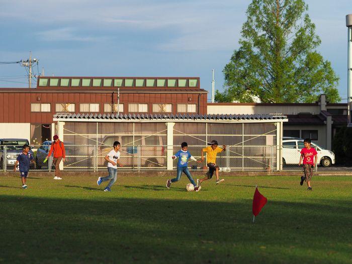 写真・図版 : 舘林では今、ロヒンギャの少年たちが地元の子どもたちを交えてのサッカーチームの活動を続けている。グラウンドの傍らではさらに小さな子どもたちも夢中でボールを蹴っていた