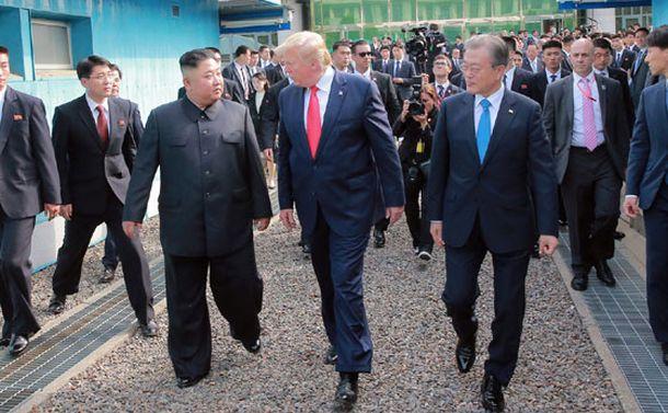 写真・図版 : 6月30日、南北軍事境界線にまたがる板門店を歩く金正恩朝鮮労働党委員長とトランプ米大統領、文在寅・韓国大統領(中央の3人)=労働新聞ホームページから