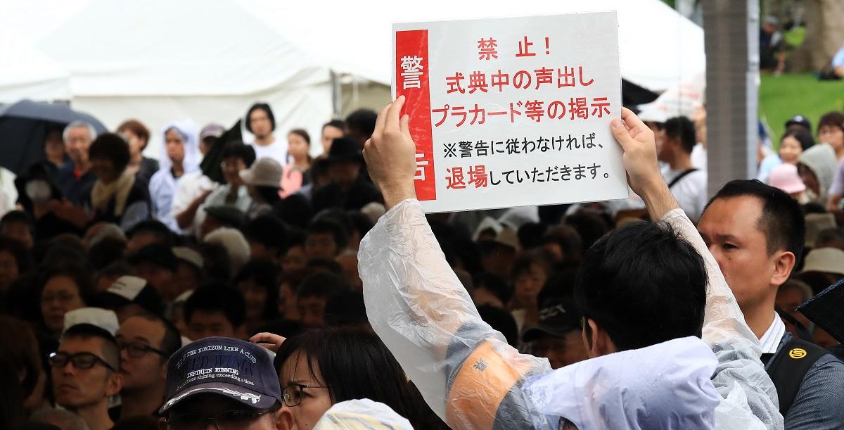 写真・図版 : 沖縄全戦没者追悼式で挨拶する安倍晋三首相にヤジが飛び、警告するボードが掲げられた
