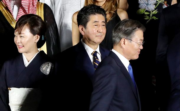 写真・図版 : 集合写真の撮影を前に、安倍晋三首相(中央)の前を歩く韓国の文在寅大統領(右)=2019年6月28日、大阪市中央区