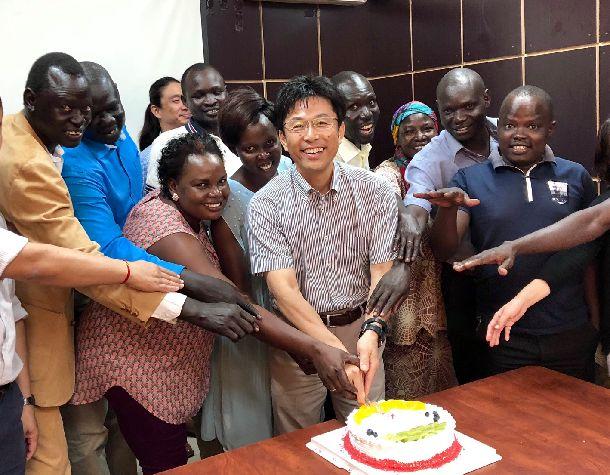 写真・図版 : 所長として赴任した時に開催してもらった歓迎会でナショナルスタッフと。 彼ら自身もしくは身内が難民経験を有する。