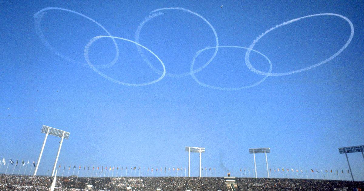写真・図版 : 東京オリンピックの開会式当日、会場上空に描かれた五輪マーク=1964年10月10日、東京・国立競技場