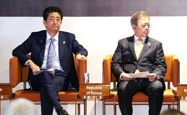 写真・図版 : APECビジネス諮問委員会(ABAC)に臨む安倍首相。右は韓国の文在寅大統領=2018年11月17日、ポートモレスビー