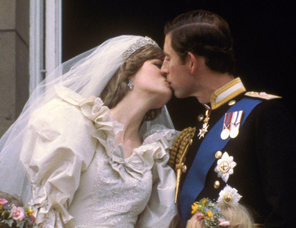 写真・図版 : 1981年7月29日、ロンドンのバッキンガム宮殿のバルコニーで花嫁、ダイアナ妃にキスをするチャールズ皇太子=AP
