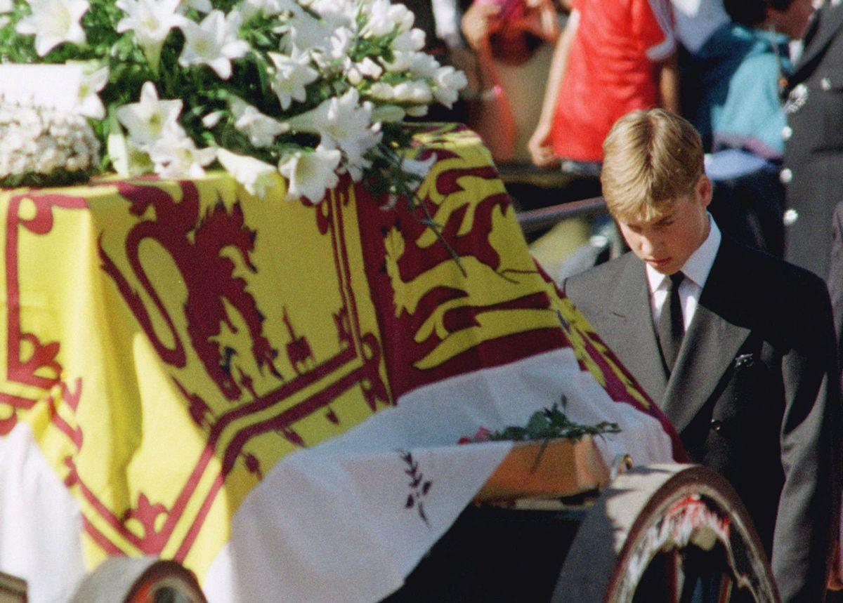 写真・図版 : 1997年、母親ダイアナ妃の棺の後ろで頭を下げて歩くウィリアム王子=AP