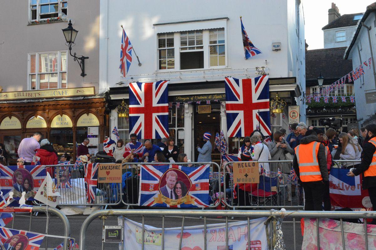写真・図版 : ハリー王子とメーガン妃のパレードが予定される沿道には英国旗が掲げられ、早朝から場所取りをする人であふれた=2018年5月19日、ウィンザー、下司佳代子撮影