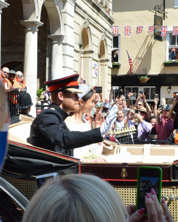 写真・図版 : 沿道の歓声に応えるハリー王子とメーガンさん=2018年5月19日、ウィンザー、下司佳代子撮影