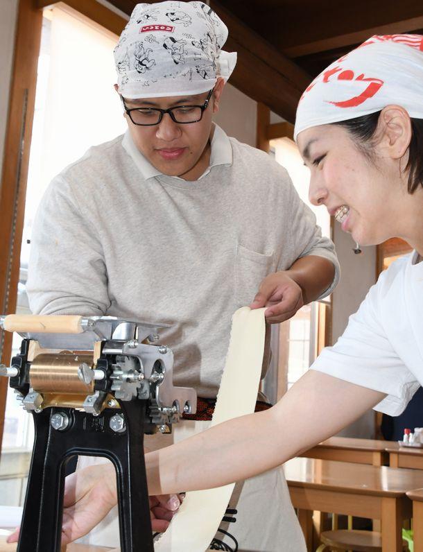 写真・図版 : ラーメンの生地を製麺機にかけるフィリピン人旅行者(左)と女性店員=2018年6月14日、京都市東山区