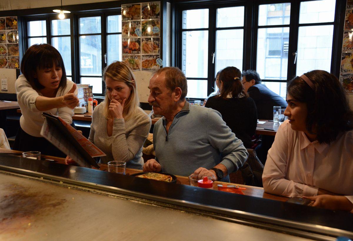 写真・図版 : ガイドの女性(左)に日本語のメニューを見せてもらいながら、説明を聞く外国人観光客たち=広島市中区