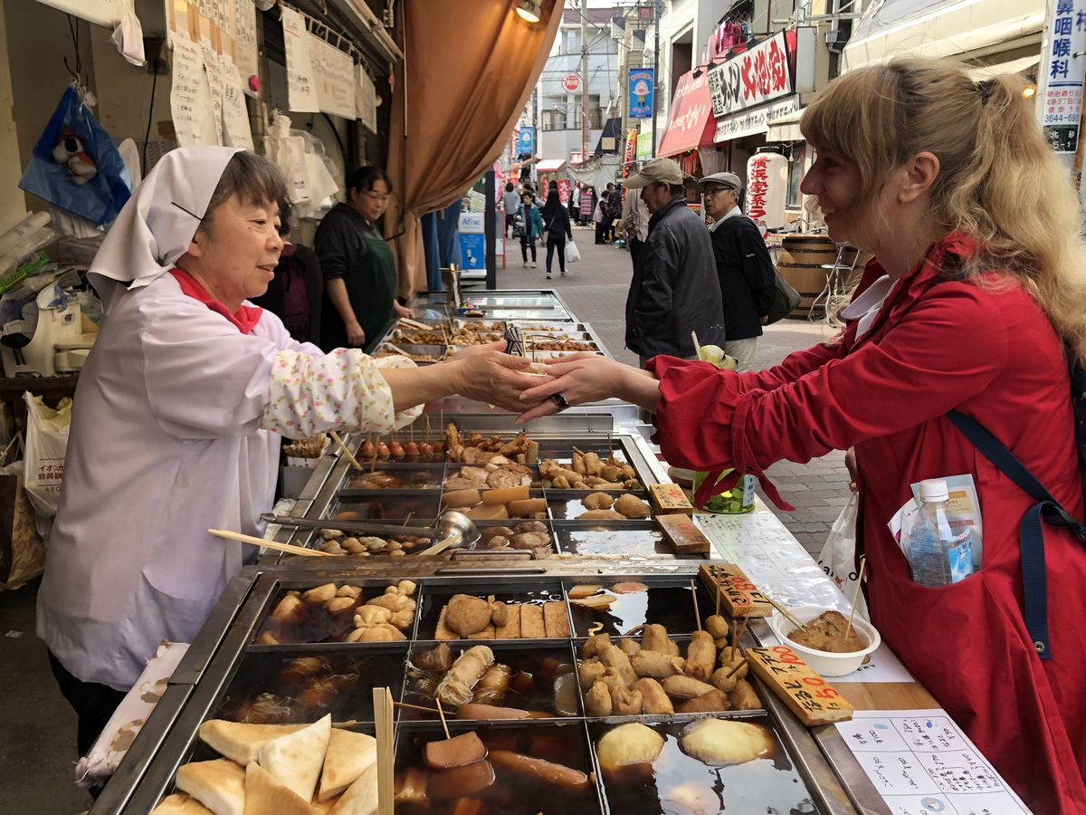 写真・図版 : 商店街でおでんを選ぶ外国人=東京都江東区
