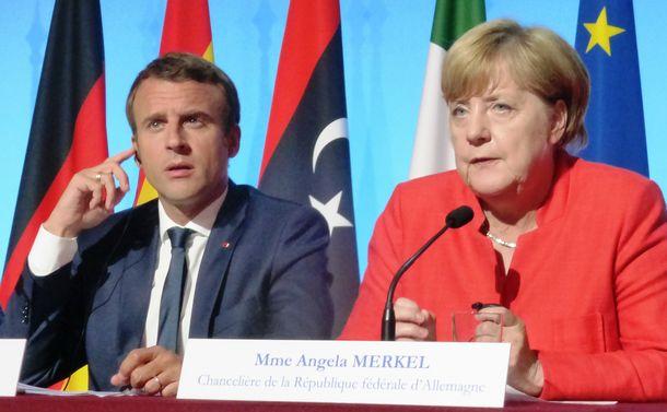 写真・図版 : 難民問題での会議を終えて記者会見にのぞんだ仏マクロン大統領(左)と独メルケル首相=2017年8月28日、パリ