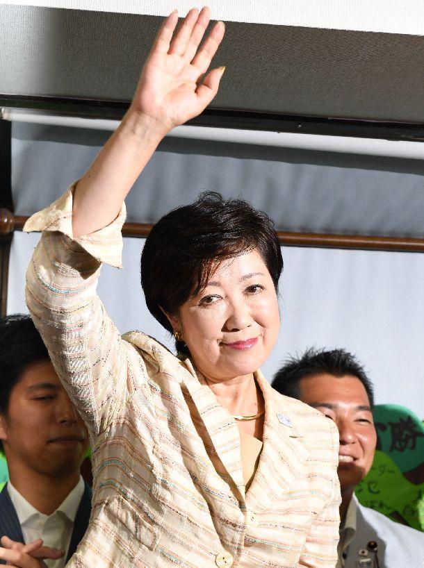 写真・図版 : 東京都知事の当選を確実にし、支援者の歓声にこたえて右手を挙げる小池百合子氏=2016年7月31日、東京都豊島区