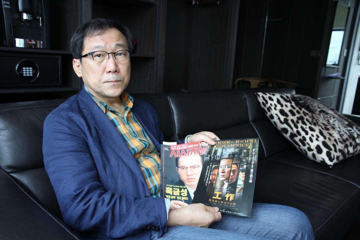 写真・図版 : キム・ダン記者。黒金星への初インタビューをまとめた1998年の雑誌と、映画『工作』のパンフレットを手に。
