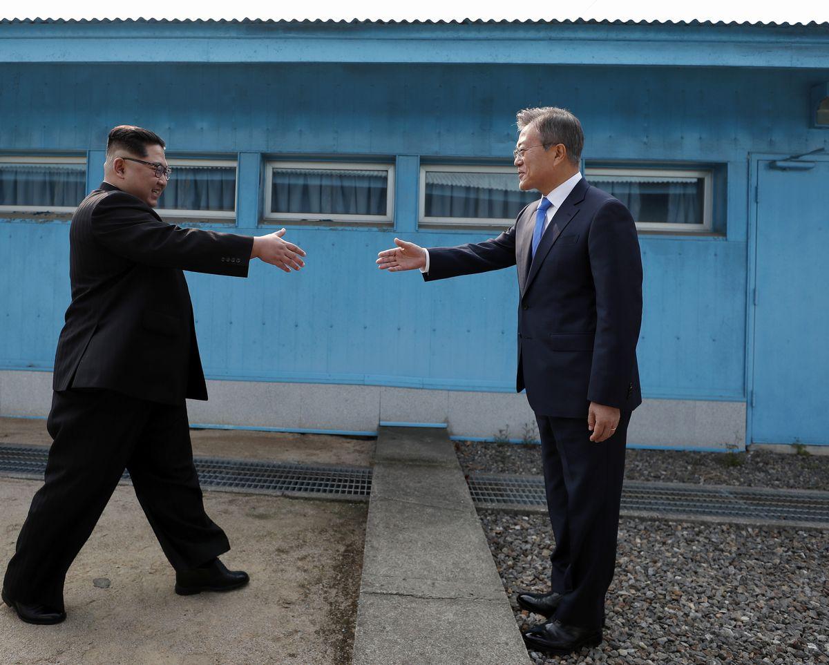 写真・図版 : 2018年4月27日、板門店で韓国と北朝鮮の軍事境界線を挟んで握手しようと手を伸ばす文在寅大統領(右)と金正恩朝鮮労働党委員長=韓国共同写真記者団撮影
