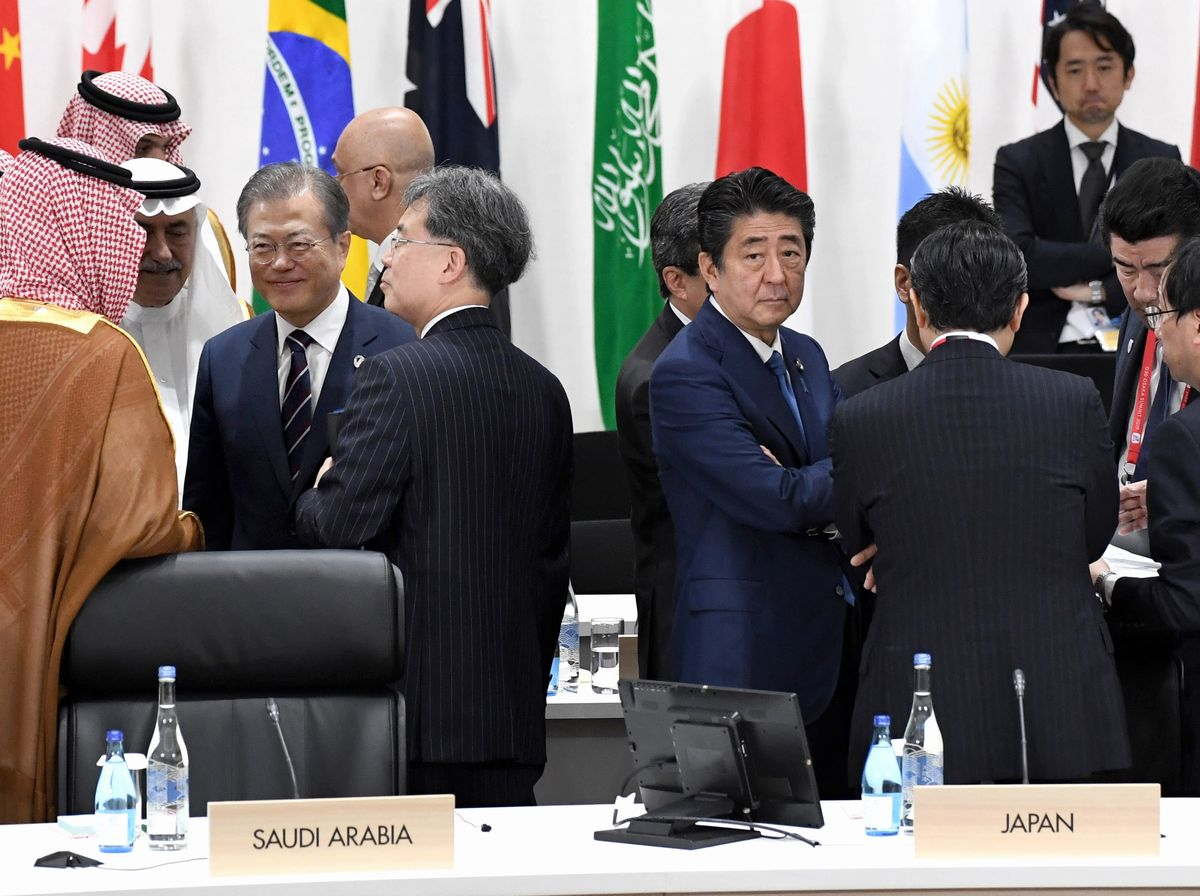 写真・図版 : 今年大阪市で開かれたG20サミットの開始を待つ安倍首相(中央右)と文大統領(左半分の中央)。この場で握手はしたが、サミット期間中の日韓首脳会談はなかった=6月29日。代表撮影