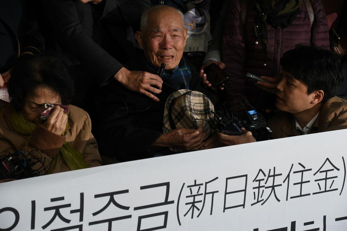 写真・図版 : 2018年10月、韓国最高裁が元徴用工の賠償請求を認める判決を出し、涙ぐむ原告の李春植さん(中央)=ソウル。朝日新聞社
