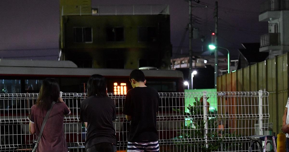 焼けた京都アニメーション第1スタジオに向かって手を合わせる人たち=2019年7月19日午後8時31分、京都市伏見区20190719