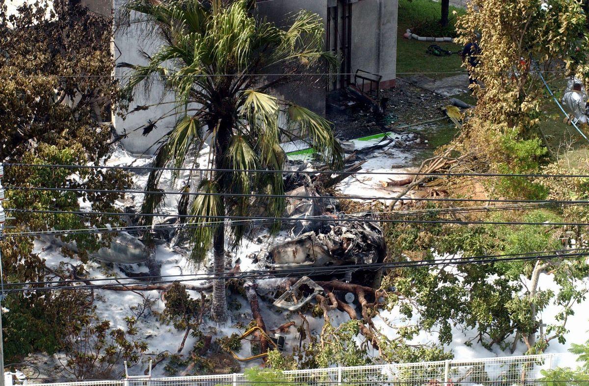 写真・図版 : 沖縄国際大学の本館に激突し、炎上したCH53D型ヘリの残骸。奇跡的に民間人の死傷者は出なかった=2004年8月13日午後、沖縄県宜野湾市の沖縄国際大学、琉球新報提供