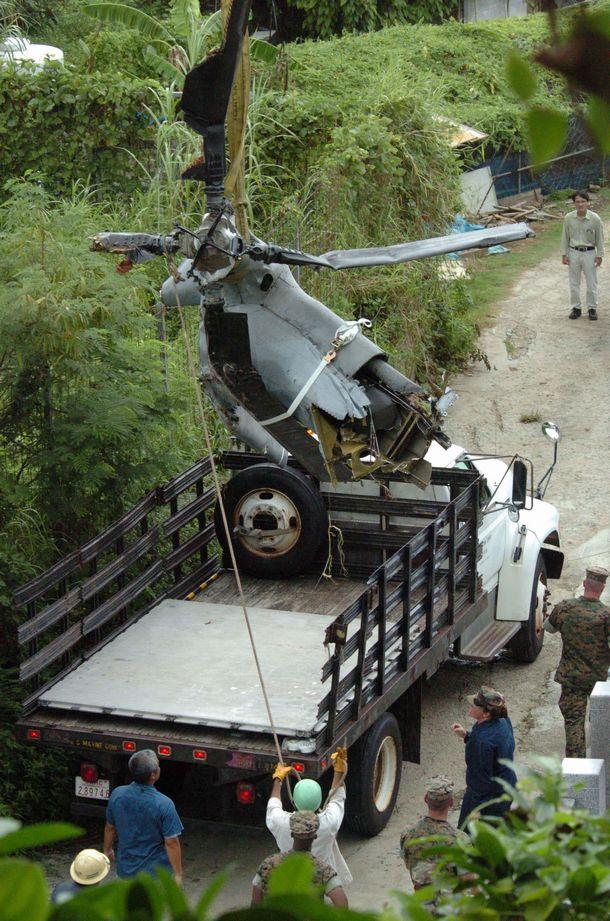 写真・図版 : 沖縄国際大学に墜落した海兵隊のヘリCH53Dの機体から飛行中に脱落した尾翼ローターを回収する米軍関係者。日本側は現場に近づくことさえできなかった=2004年8月16日、沖縄県宜野湾市志真志公民館近く、琉球新報提供