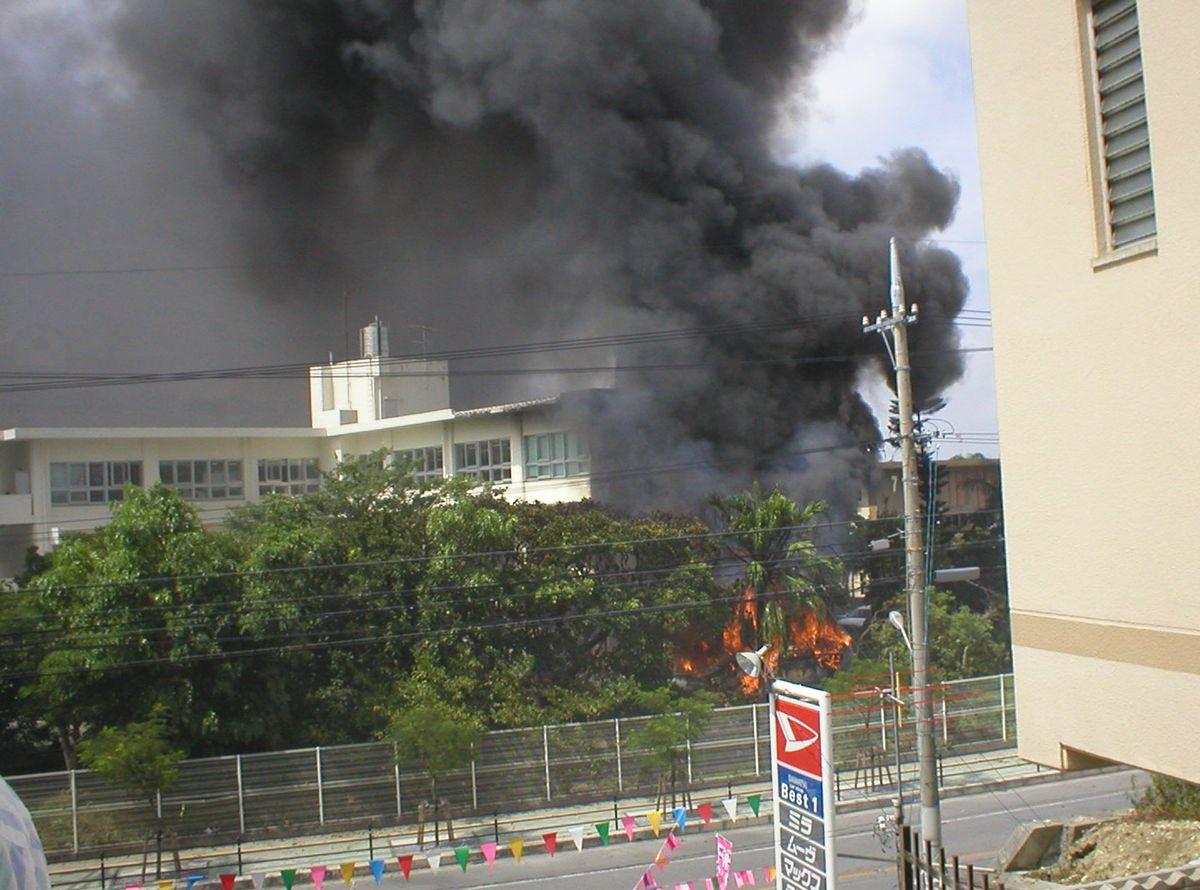 写真・図版 : 大学本館に激突した後、黒煙を上げて激しく炎上する米海兵隊のCH53D型ヘリコプター=2004年8月13日午後、宜野湾市宜野湾の沖縄国際大学、琉球新報提供