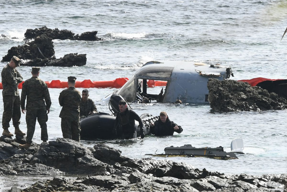 写真・図版 : 大破したオスプレイの機体付近を調べる米軍関係者ら=2016年12月15日、沖縄県名護市安部、長沢幹城撮影