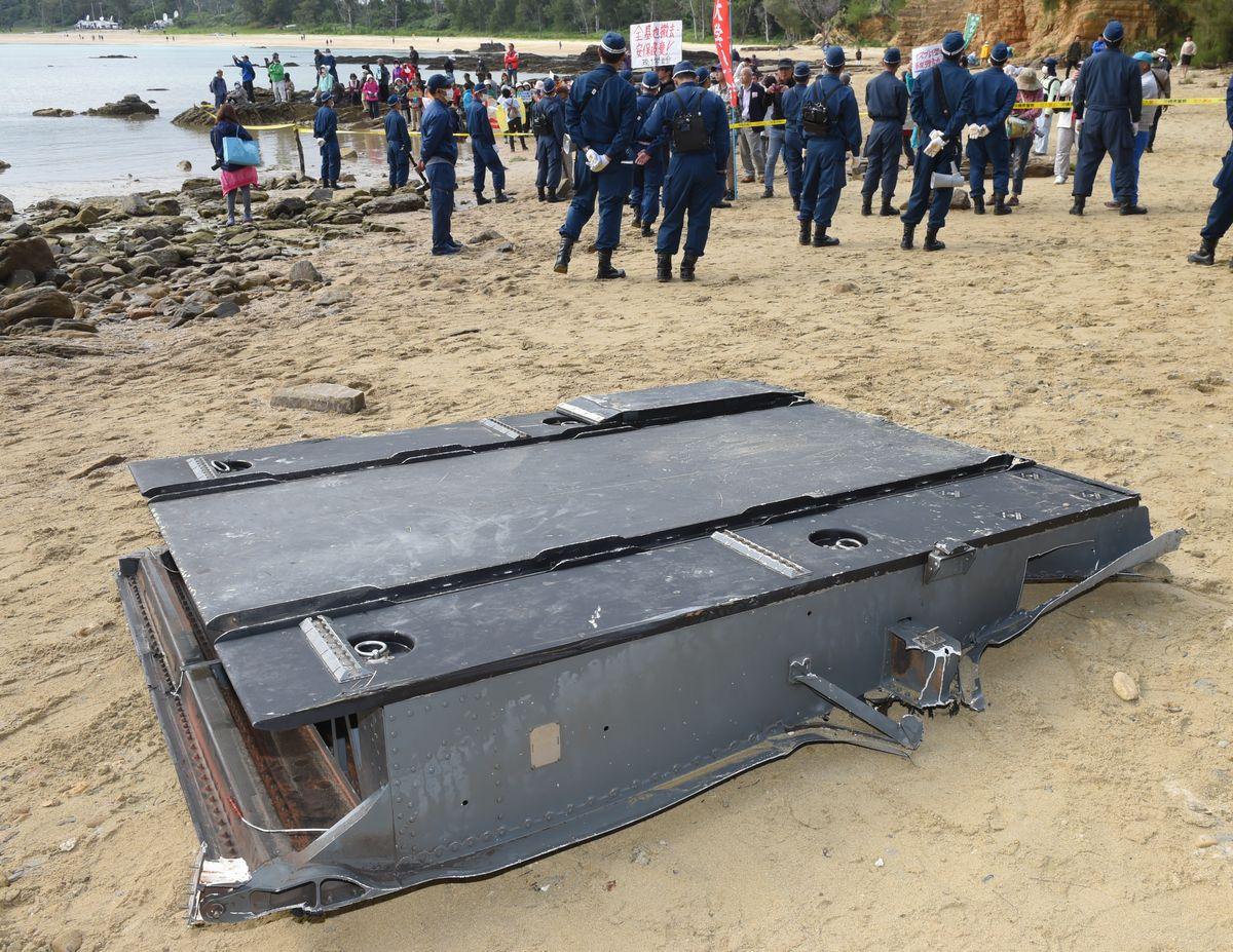 写真・図版 : オスプレイが大破した現場近くの砂浜には海上から回収した機体の一部とみられる部品が置かれていた=2016年12月14日午後1時34分、沖縄県名護市安部、長沢幹城撮影