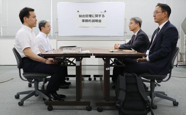写真・図版 : 日韓貿易の当局者会議で韓国側への説明に臨む経済産業省の担当者(左側)。殺風景な部屋と服装の違いが、日本の冷ややかな態度を際立たせた=2019年7月12日、東京・霞が関