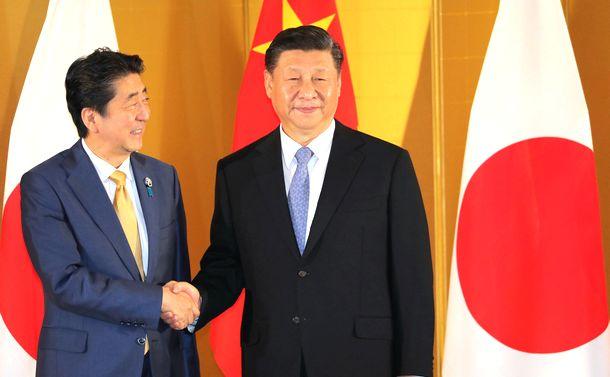 写真・図版 : 中国の習近平国家主席(右)と握手する安倍晋三首相=2019年6月27日、大阪市北区
