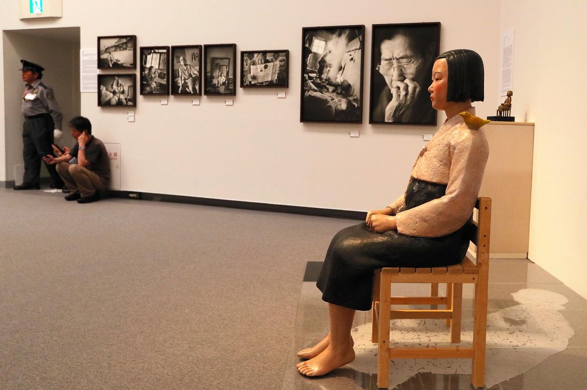 写真・図版 : 「表現の不自由展・その後」に出展されていた「平和の少女像」と元慰安婦の写真。これらの作品が河村たかし市長などから抗議された=愛知芸術文化センター