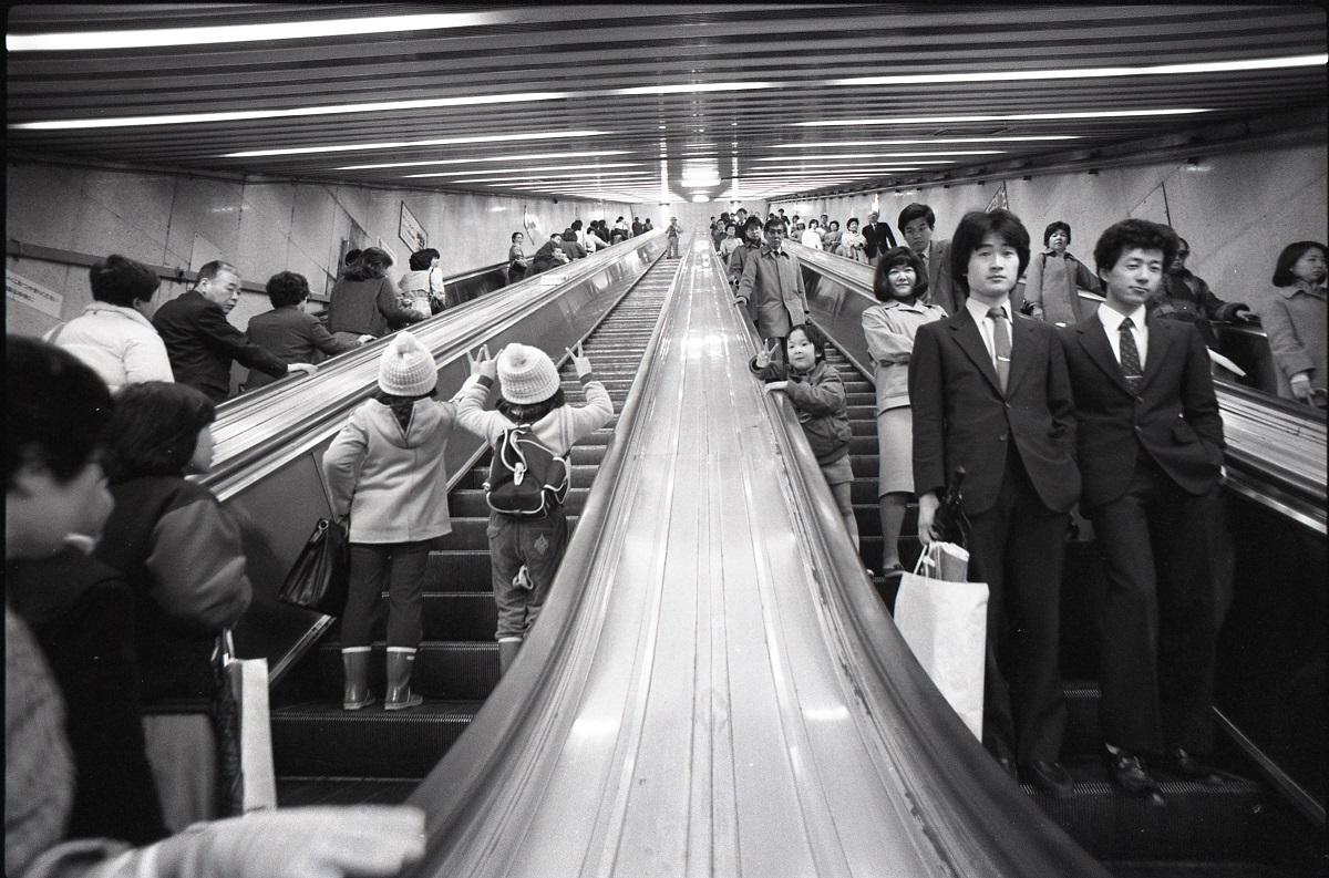 写真・図版 : 地下鉄千代田線の新御茶ノ水駅に1969年できた長さ41メートルのエスカレーター。右側を空けて立つ習慣は、89年頃からこの駅で自然発生的に始まったといわれるが、この写真が撮影された84年にはまだ両側に立つのが普通だった