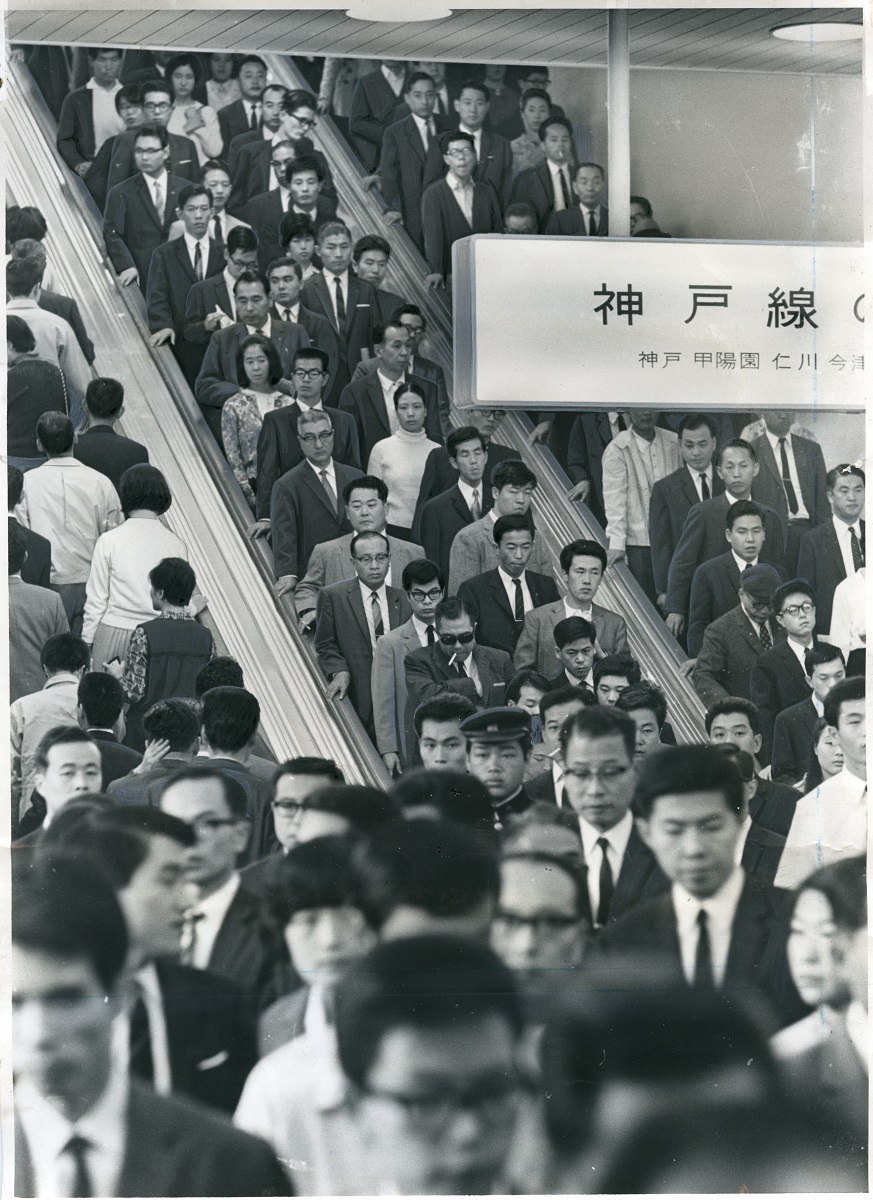 写真・図版 : 阪急梅田駅のエスカレーター。両側に並んで立っているように見えるが、この時点で「左側を空けるように」というよびかけも行われていた=1967年10月