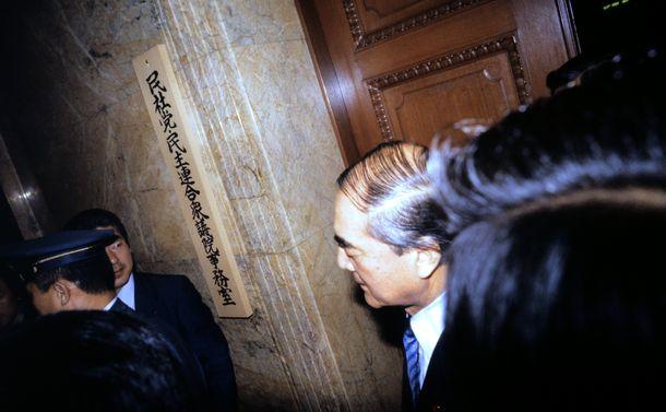 写真・図版 : 「売上税」法案が事実上廃案に追い込まれた未明、「民社党・民主連合衆議院事務室」と書かれた部屋の前の中曽根康弘首相。疲労の色が濃い=1987年4月24日未明、東京都千代田区永田町