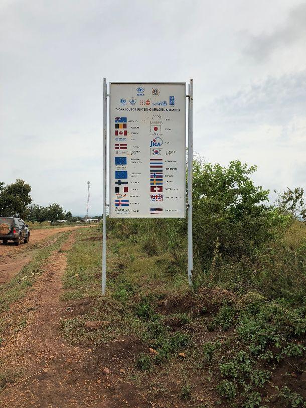 写真・図版 : ビディビディ難民居住区が近づくと見えてくる看板。「ウガンダにいる難民へのサポートありがとうございます」と書かれ、日本やJICA他、支援している国の国旗や機関、団体のロゴが記されている。