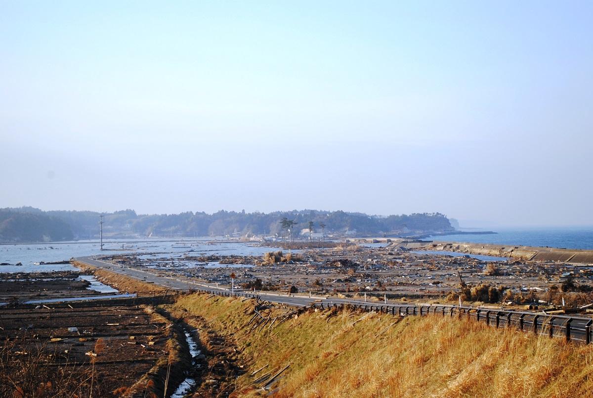 写真・図版 : 南相馬市小高区の浦尻部落(手前)。中央あたりに津波を耐えた6本の松がうっすらと見える=2011年4月7日、筆者撮影