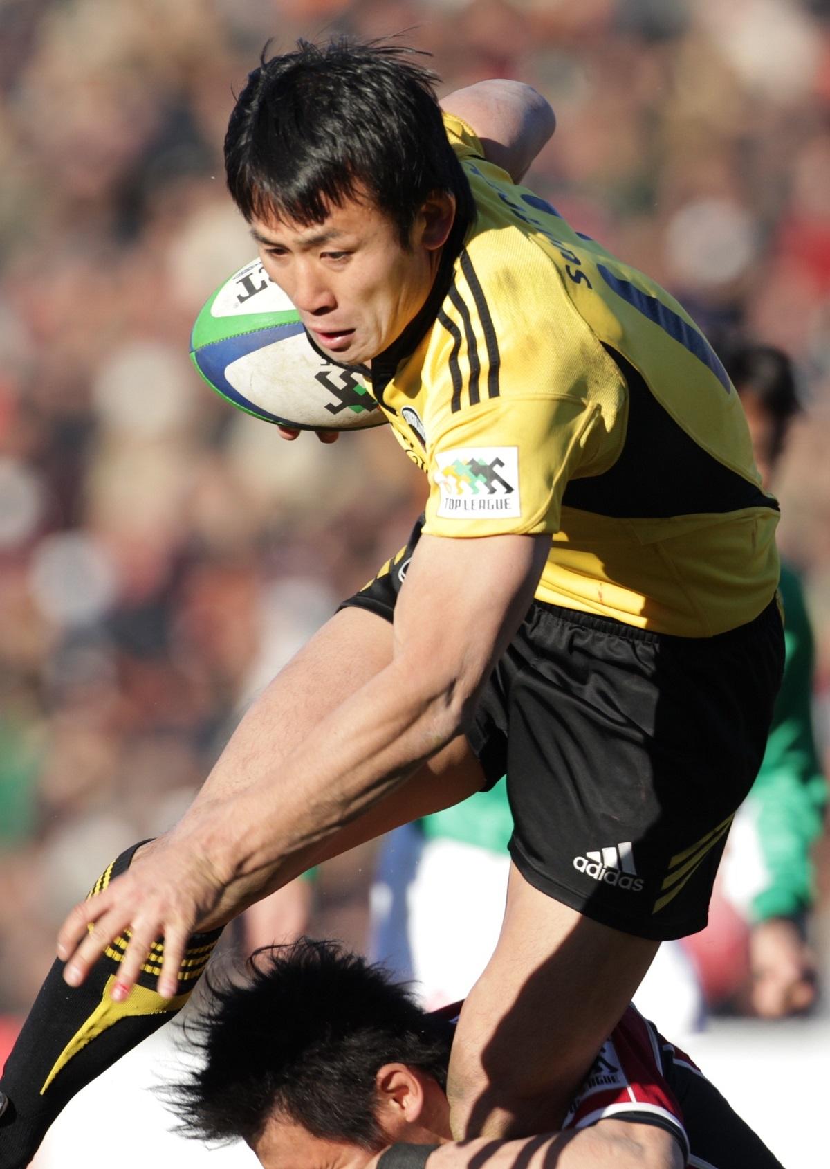 写真・図版 : タックルをかわして突進するサントリーの小野沢宏時選手=2011年1月10日、東京・秩父宮ラグビー場
