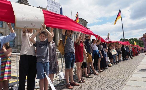 ドイツ連邦議会の建物を赤い布を掲げて取り囲み、地球温暖化対策を訴える人たち=2019年6月28日、ベルリン、野島淳撮影