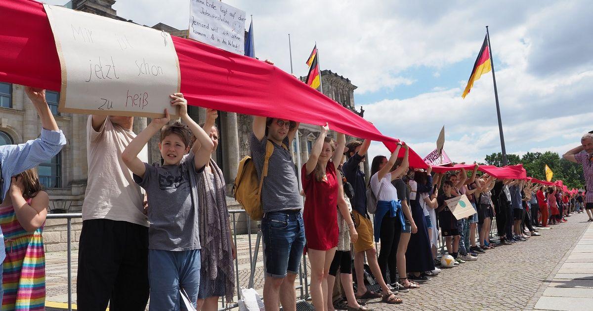 写真・図版 : ドイツ連邦議会の建物を赤い布を掲げて取り囲み、地球温暖化対策を訴える人たち=2019年6月28日、ベルリン、野島淳撮影