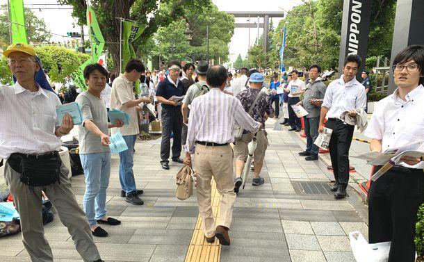 写真・図版 : 最寄り駅から靖国神社の参道に⾄る歩道では、様々な「主張」を訴える人たちが並んだ=2019年8⽉15⽇、東京・九段北