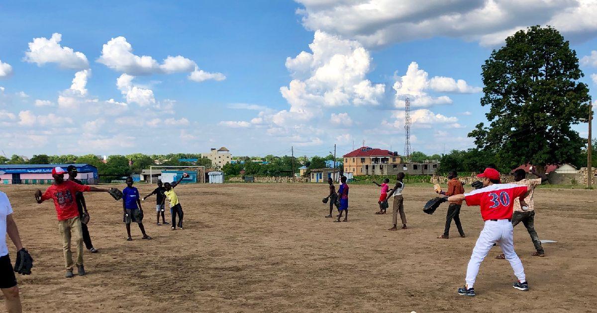 写真・図版 : アフリカの空の下でキャッチボールをする南スーダンの子供たち。