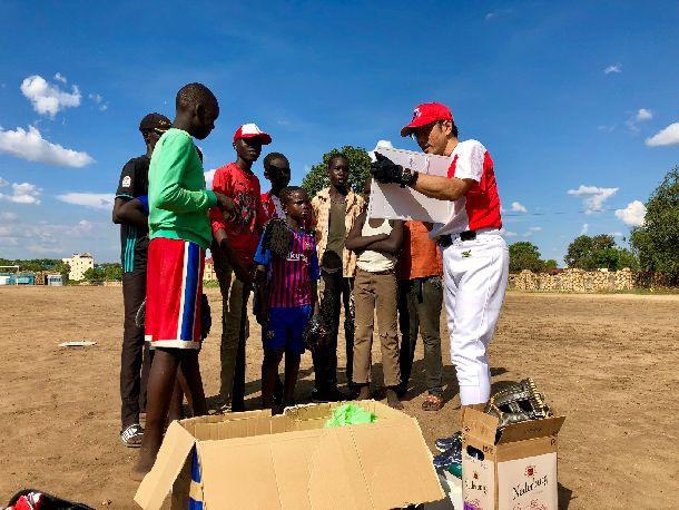 写真・図版 : 開始前ミーティング。野球の練習を見たこともない子供たちに、まずは練習の流れを、野球ボード(野球場が描かれ、野手がマグネットで張り付いているもの)を使って説明