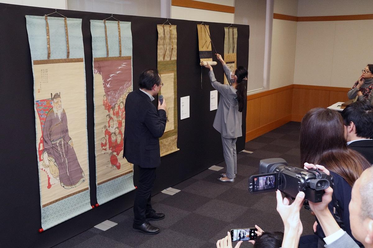 写真・図版 : 急きょ手作りした壁に絵を掛けて紹介した「へそ展」の記者発表