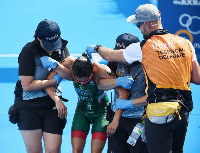 写真・図版 : 女子トライアスロンのテスト大会でゴール後に倒れ込み、スタッフに水で冷やされる選手=2019年8月15日、東京都港区のお台場海浜公園