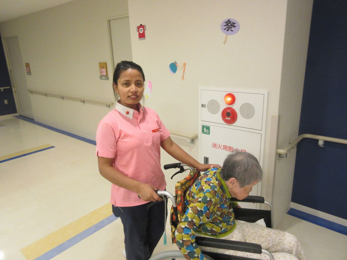 写真・図版 : 車いすの利用者を介助する外国人スタッフ=アゼリーグループ提供