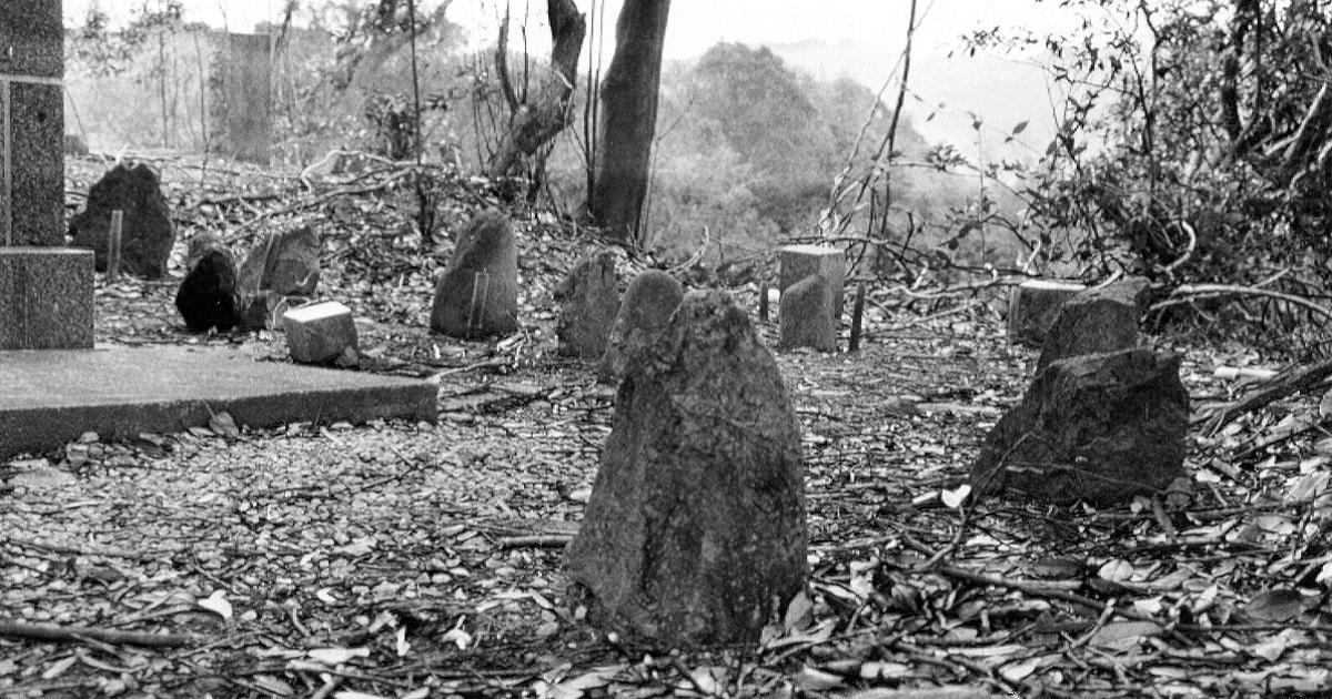 写真・図版 : 炭鉱の地、筑豊に残る朝鮮人労働者の墓。墓石は石炭などの採掘で発生した捨石(ボタ石)=1992年、福岡県田川郡添田町